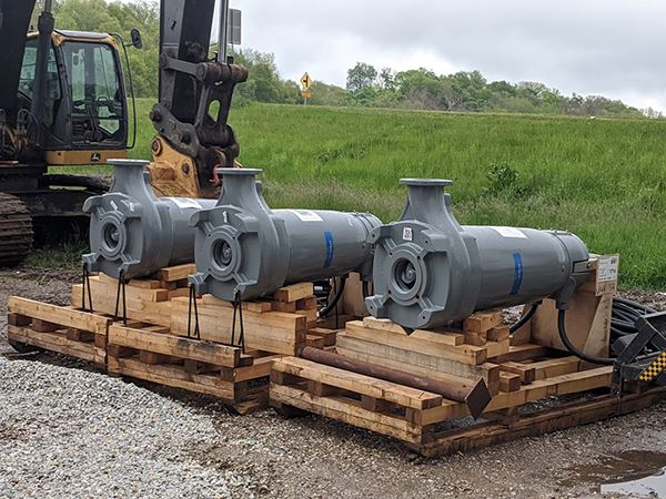 Three large mechanical pumps sitting on wooden pallets