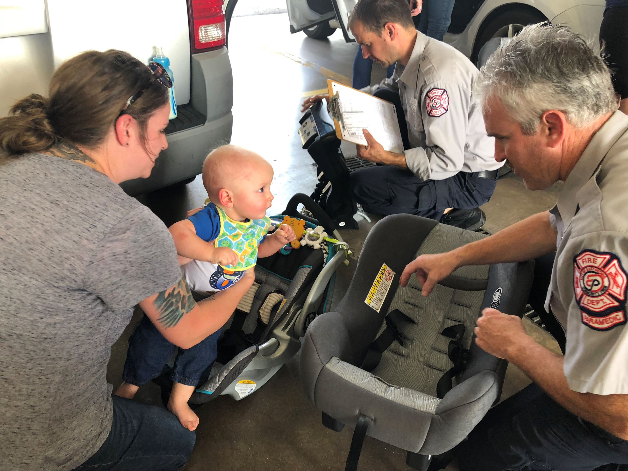 Mom and firefighters checking baby's car seat